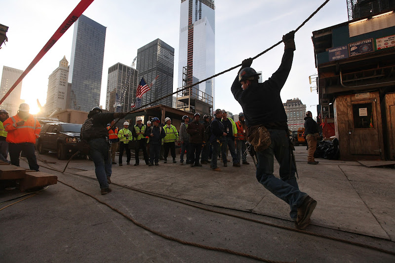 Photo: NEW YORK, NY - DECEMBER 12:  Workers pull a rope as they prepare the first piece of the spire to be hoisted atop One World Trade Center on December 12, 2012 in New York City.  The first of 18 sections of spire was hoisted atop the 104-story building by crane this morning.  (Photo by Mario Tama/Getty Images)