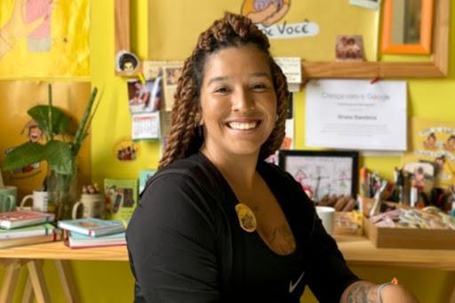 Uma mulher sentada sorrindo e olhando para a câmera. Ao fundo há uma parede amarela cheia de ilustrações e ferramentas de desenho.