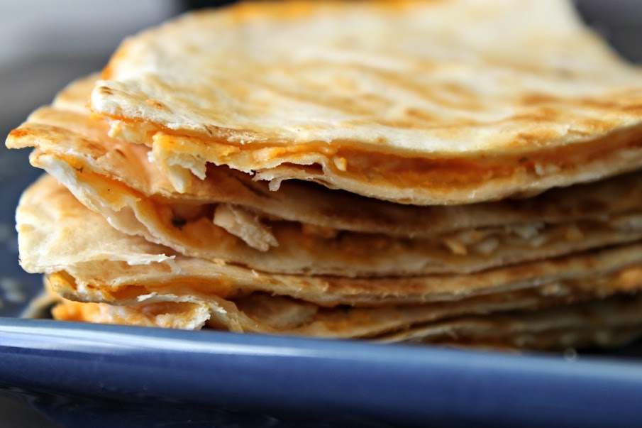 Stacks of Buffalo Chicken Quesadillas served with a side of queso or salsa are great for tailgating