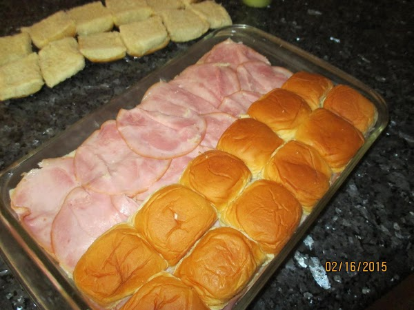 Layer about half of the ham onto the rolls. Arrange the swiss cheese slices...