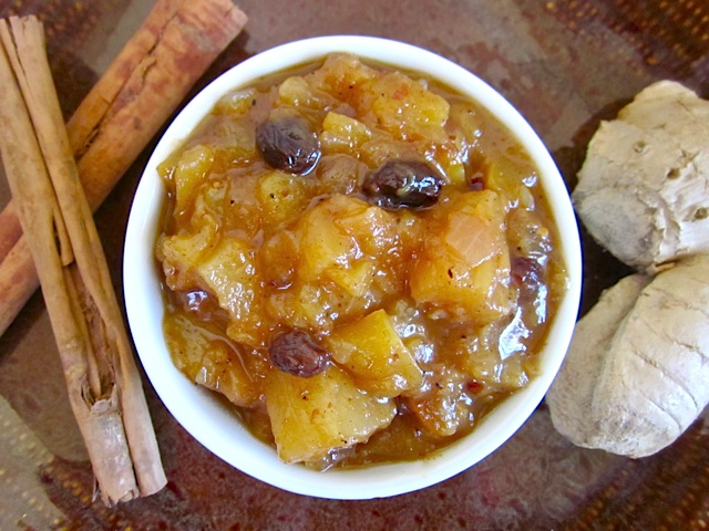 Mango Pineapple Chutney in white bowl with cinnamon sticks and bread on the side