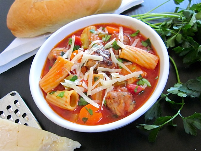 hearty meatball soup in white bowl with garnishes on side