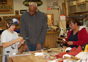 Photo: Jake shows Benji how to assemble the pen while Imelda Rocha glues the tubes into blanks.