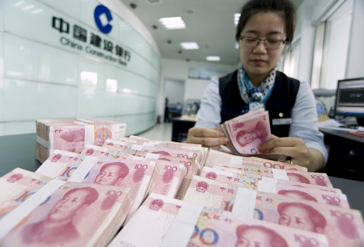 A clerk counts Chinese 100 yuan banknotes at a branch of China Construction Bank in Hai'an, Jiangsu province in this June 10 2014 file photo. Picture: REUTERS