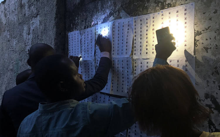 Voters use their cellphones to light as they look for their names on the voter's roll outside a polling station during the presidential election in Kinshasa, Democratic Republic of Congo, on December 30 2018.