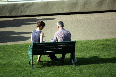 People sitting on a bench at Ascot Racecourse in England