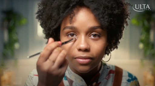 Woman of color applying makeup with Ulta Beauty logo watermarked over image