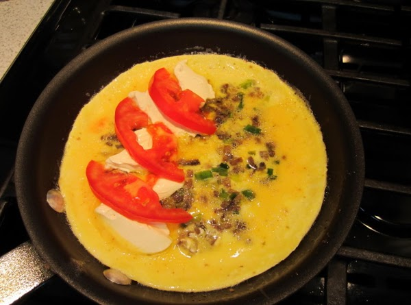 Once the eggs are almost set, spread cream cheese on one side of the...