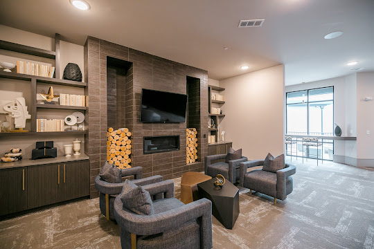 Upscale lounge seating area with a mounted TV, plush seating, and decorative shelving accents