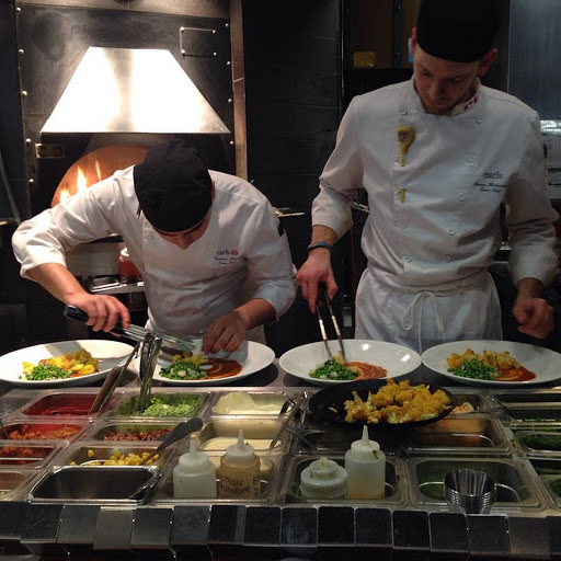 Two kitchen partners at a kitchen station assembling food onto a plate.
