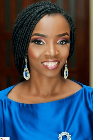 A photo of Ronke, who has short hair and is wearing makeup, smiling.