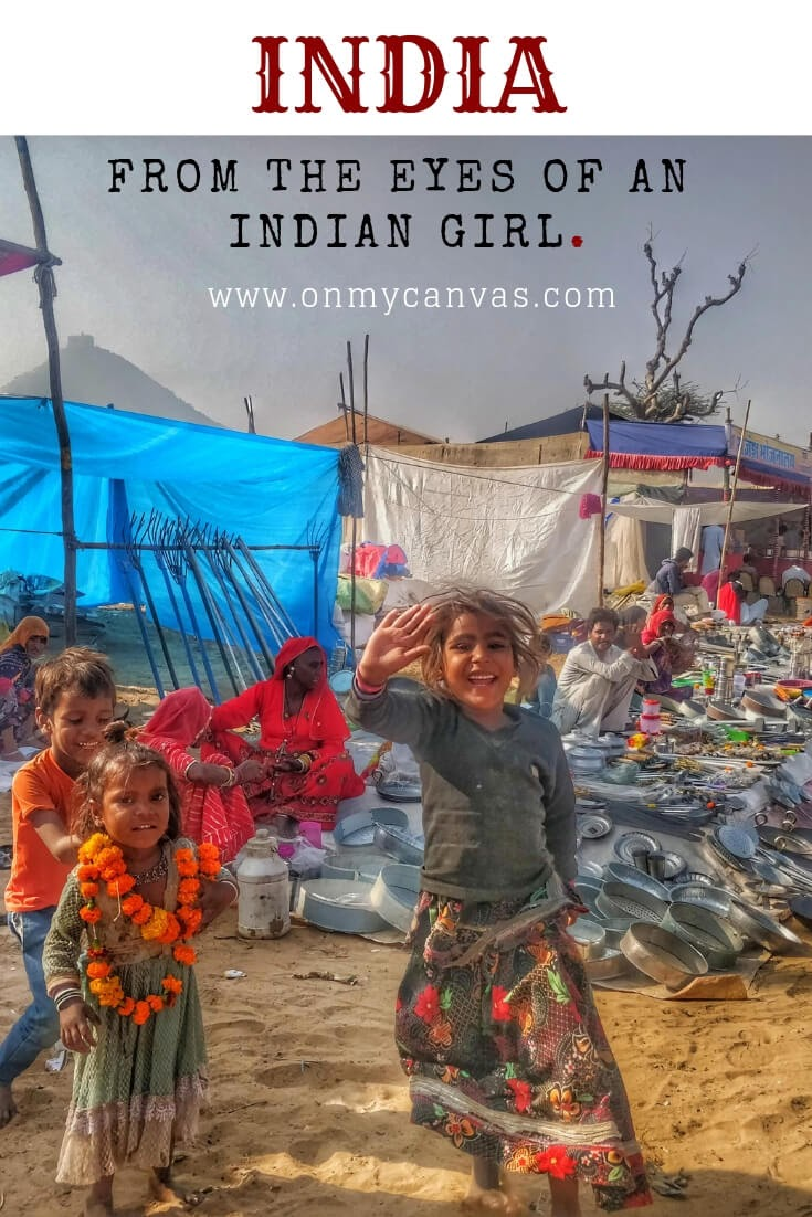 A little girl smiling and saying hi in pushkar mela rajasthan india photo is being used for the pinterest image for a indian woman story about India