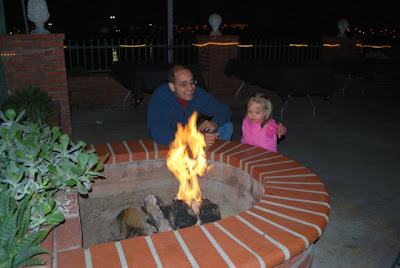 This is a photo of a man and his little daughter next to the fire pit on the deck of the Ports O' Call bar in Port of San Pedro, CA.