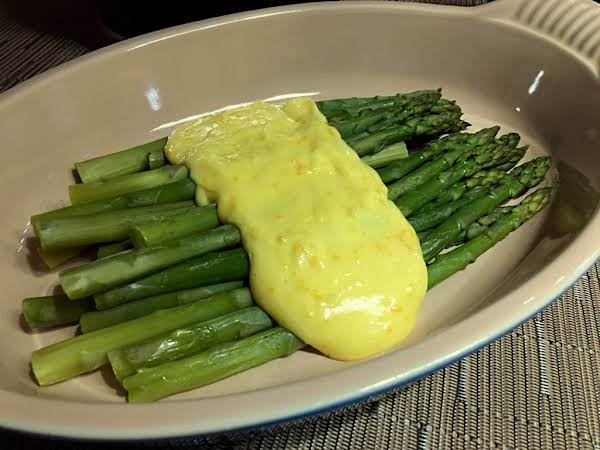 A Bunch Of Asparagus Sitting On A Serving Dish With A Sauce On Top.