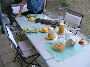 Photo: Day 11 begins with another one of Josy's wonderful breakfasts on the back terrace, including 6 kinds of jam, and lavender honey (cheeses, fruit, yogurt, baguettes, and croissants still to come). Note also the half lemon studded with cloves at middle right - a common Provencal device to keep away wasps (although Josy says a small hunk of raw meat hung at the far end of the terrace works better).