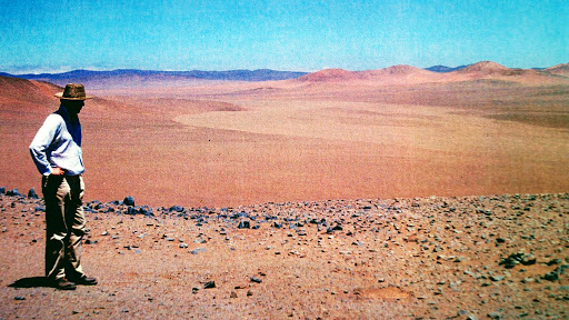 Hombre con un sombrero parado frente a un desierto