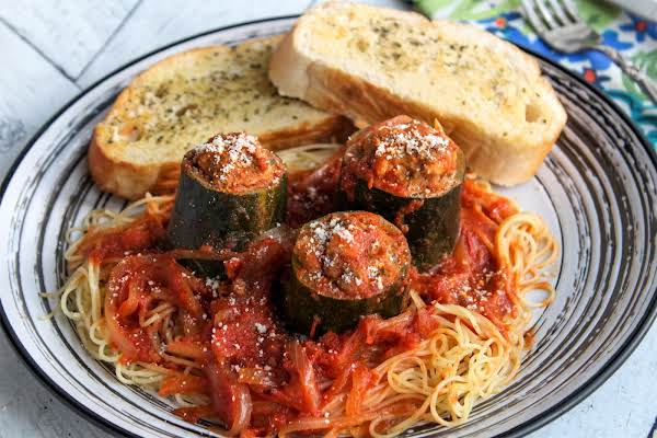 Italian Stuffed Zucchini On A Plate With Spaghetti.