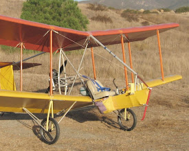 "Photo: The pilot flies completely in the open. The total recovery system (the emergency parachute that brings down the pilot and airplane together) is in the purple bag. The elevator and rudder control lines can be seen running under the wing from the nose section back to the pulley block. That snazzy curved control stick was made from an aluminum walking cane, and the seat was made for a boat (both from Walmart). The four point seat belts are the push button, automotive ""dune buggy"" type, because I could not find a suitable aircraft belt (you do not want an aircraft quick release!). Just below the top of the nose tube, the handle for pull starting the engine can be seen, above the pilot's head where it can be reached in flight."