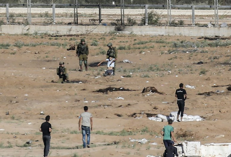 Israeli soldiers drag away an injured Palestinian who tried to approach the border fence east of Jabalia in the northern Gaza Strip on June 27 2018