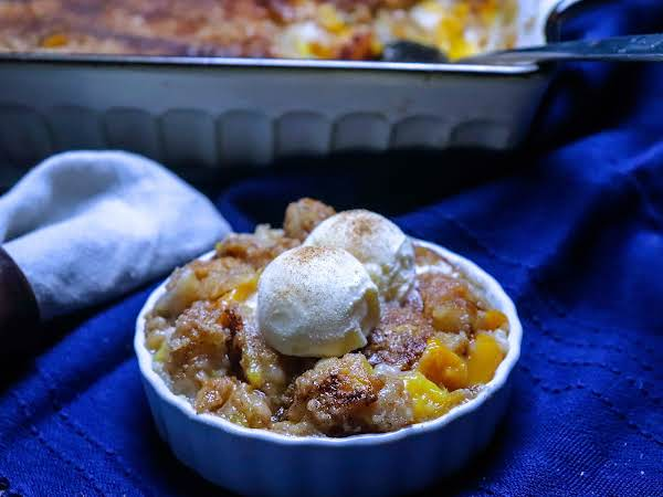 A Small Bowl Of Peachy Peach Cobbler With Ice Cream.