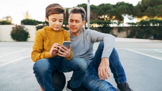 man and young boy looking at phone together