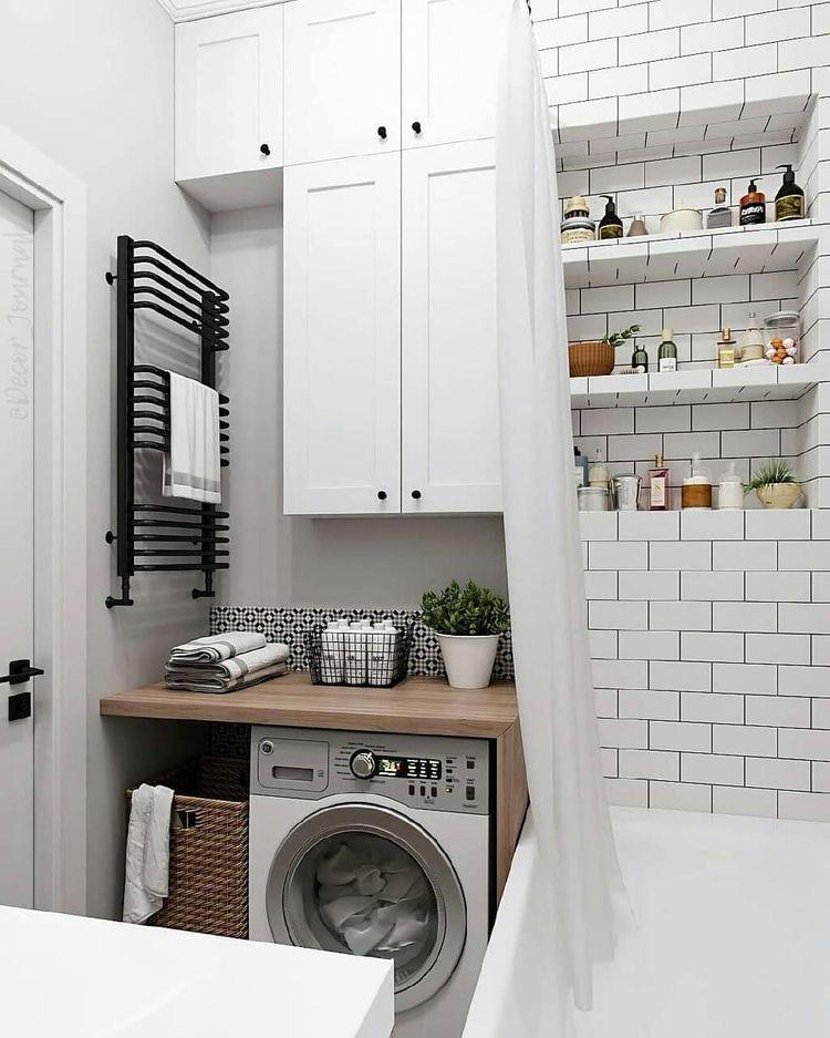 стиральная машина в ванной под столешницой с черным полотенцесушителем