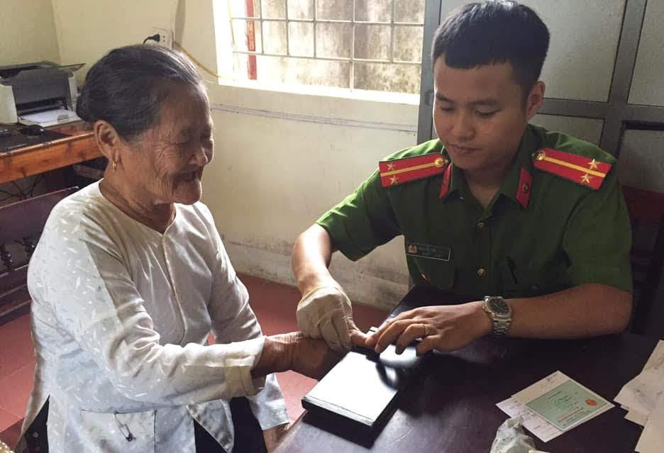 Cán bộ Công an TX Thái Hòa làm thủ tục cấp phát CMND cho người già