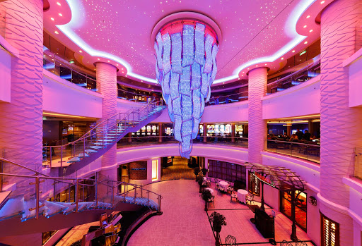 Norwegian-Escape-Atrium - Guests of  Norwegian Escape are greeted in the atrium by a stunning chandelier that changes colors, shifting from clear to aqua, pink, lavender and other colors on a varying schedule.
