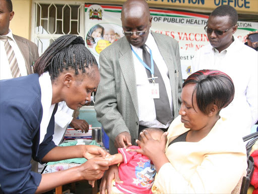 A nurse injects a minor with a vaccine during the launch of the five-day measles vaccination campaign in Naivasha in 2014.