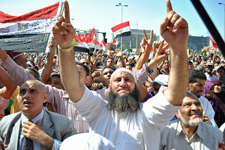 """Photo: A Muslim raises his arms in approval as a chant is echoed all over the square: """"the people want the downfall of the regime"""""""