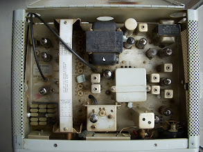 "Photo: Inside the 75S-3B receiver. This rig has probably had cigarette smoke blown at it for about 35 years. There is a layer of brownish gunk coating everything. At the very top of the photo you can see a dark brown patch of convection-enhanced smoke staining which will wash away. The styrofoam ""peanuts"" are left over from it being shipped to the previous owner after repair - someone decided to fill the inside with these things. Ugh."