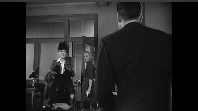 """Photo: Shot 9 of 18.  Duration: 11 seconds.  MLS. The same camera set-up as before.  Over-the-shoulder. The substitution of one woman for the other is nicely captured in this frame in which Effie tents Spade's unseen face for his reaction to Miss Wonderly, the """"knock-out.""""  We get a good look at Miss Wonderly as she walks towards Spade and the camera in this long-ish shot.  Her hat, fur, and purse tell us she is A Lady.  But in this genre, we may know already to be skeptical of appearances.  The same camera set-up as Shot #6."""