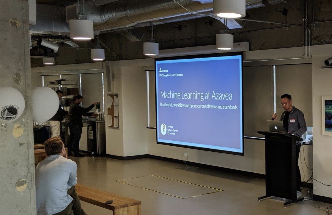 A photograph of Aaron Su giving a talk at a happy hour at the fourth STAC sprint in San Francisco.