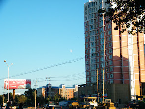 Photo: an early moon appear in bright dusk near QRRS' skyscraper.