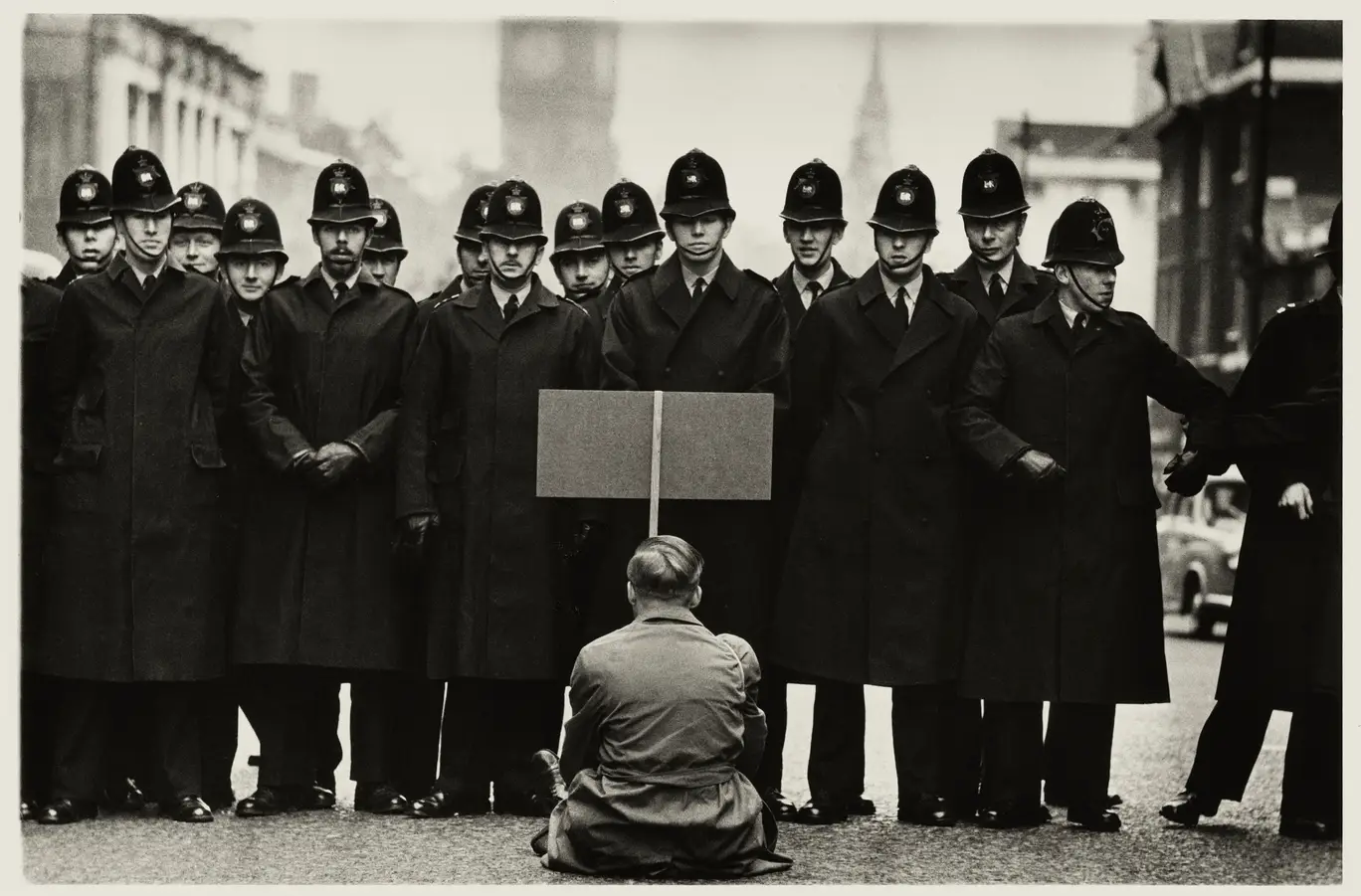 A black and white photo of a single protestor sat in front of a line of police, by famous photographer Don McCullin