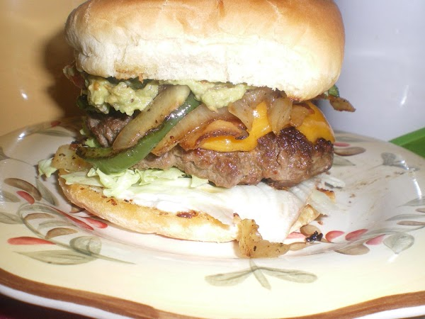 Top bottom bun with lettuce, patty, bacon, peppers and onions, guac, then sliced fire...