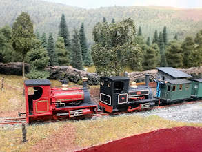 Photo: 129 Two Hunslets, Lilla in black and Cackler in red, built by Jon just before the show, pass Plas Halt with a goods train headed by a pair of quarrymen's coaches. Both locos are built from Five79 (ex Chivers) kits and Lilla has been modified with a straight footplate, with the resultant taller cab. Both locos are mounted on the Minitrains F&C outside frame chassis .