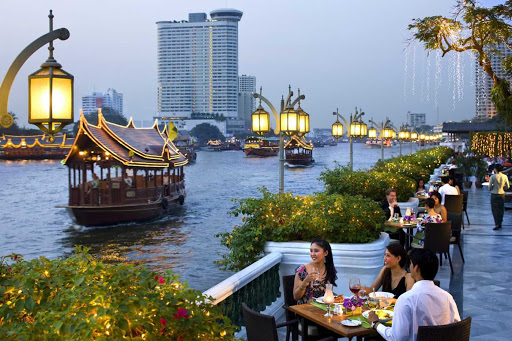 bangkok-restaurant-riverside-terrace - Watching the action along the Chao Phraya river at dusk at the Riverside Terrace, part of the Mandarin Oriental in Bangkok.
