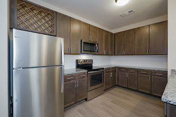 Stainless steel refrigerator, stove, and microwave, brown cabinets with built in wine rack, and light countertops