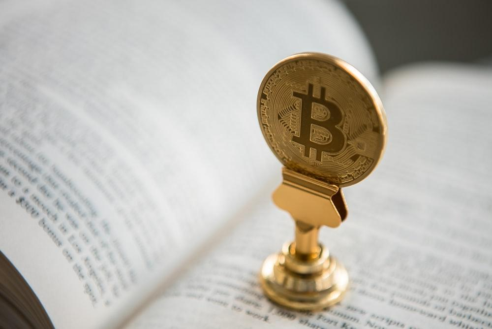bitcoin on gold stand on top of book