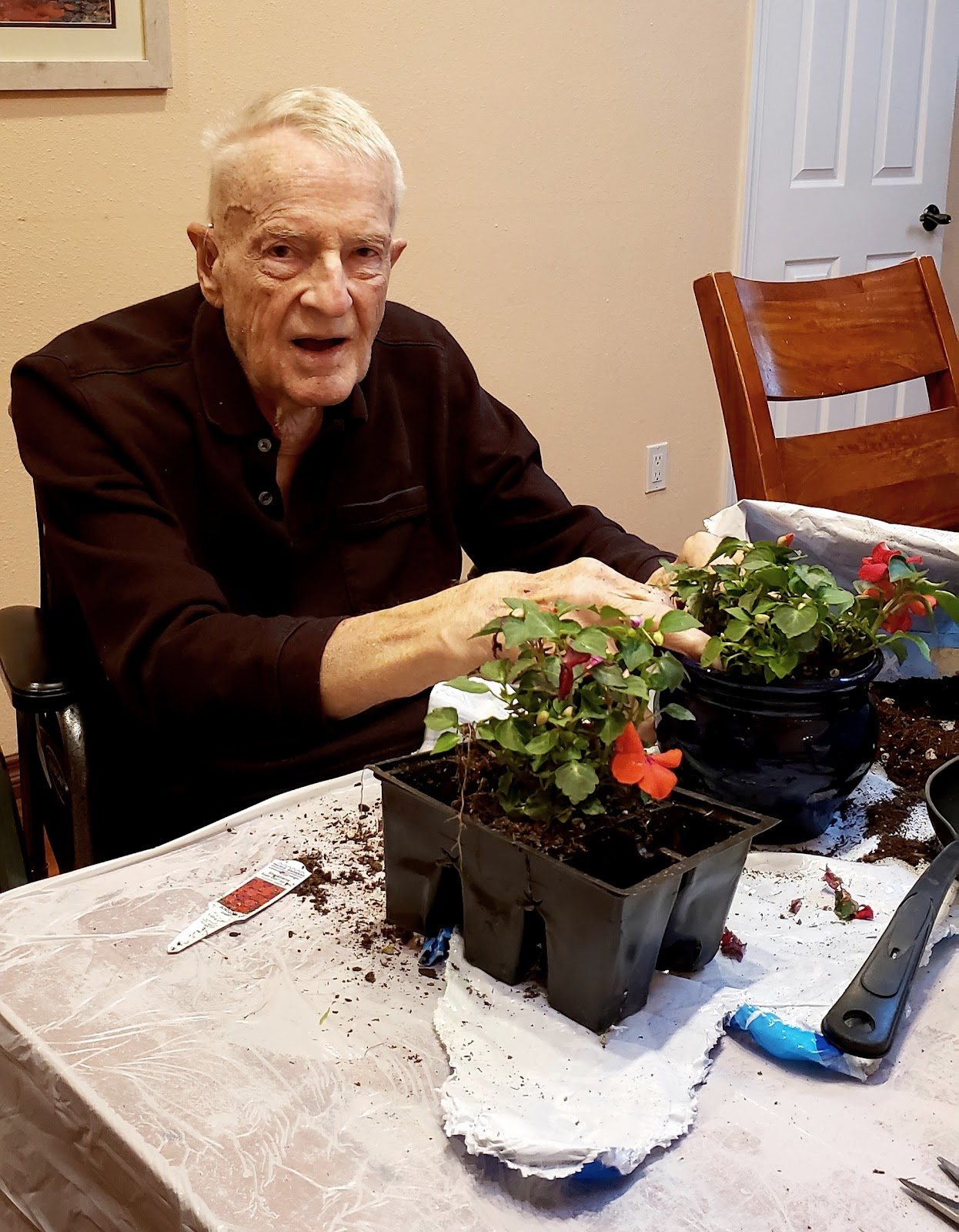 John potting some flowers after he experienced a traumatic brain injury.
