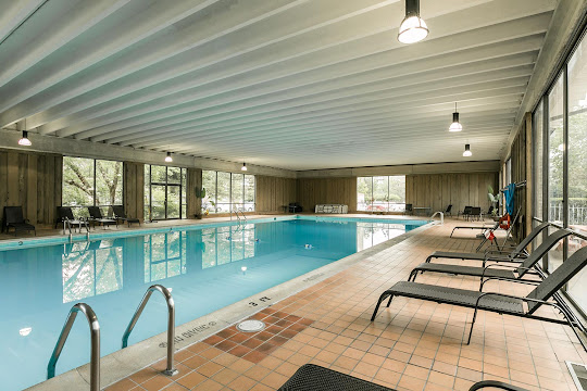 Indoor swimming pool with several floor-to-ceiling windows and lounge chairs surrounding