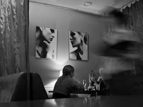 [DREI JUNGE FRAUEN IN TOTALE SITZEN IN EINEM CAFÉ UND TRINKEN WEIN UND ORANGENSAFT. SIE UNTERHALTEN SICH ANGEREGT. NUR DIE FRAU IN DER MITTE IST ZU ERKENNEN. DIE ANDEREN 2 ZFRAUEN WEDNEN SICH IHR ZU.]
