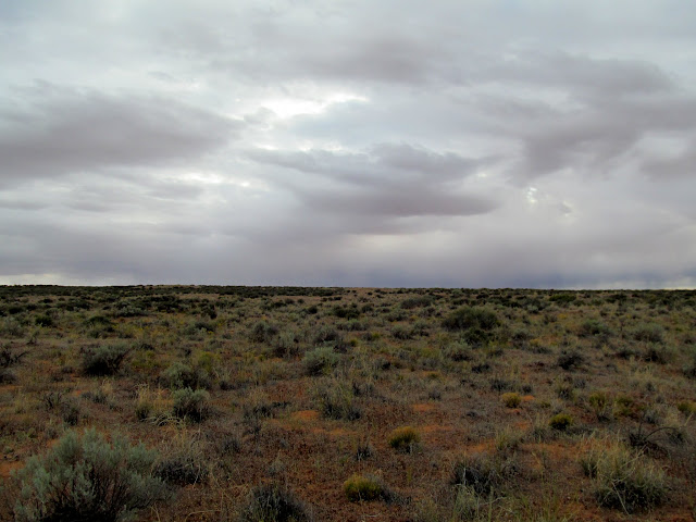 Dark skies, with flat terrain belying the canyon country ahead