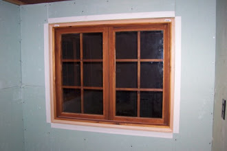 Photo: Here's a close up of one of the windows. I wanted to show how I finished the drywall around the window and hid the spaces and gaps. I purchased paper corner beads and an adhesive which afixed the corner beads around the drywall and onto the window frame. I also purchased 90° wood corner trim that will overlap the corner bead and cover the gaps around the window (which have been filled with expanding insulation). You can barely see the 90° pieces in this picture (you can see their UPC codes though), but they'll be stained to match the rest of the window, so it should look pretty good when it's all done!