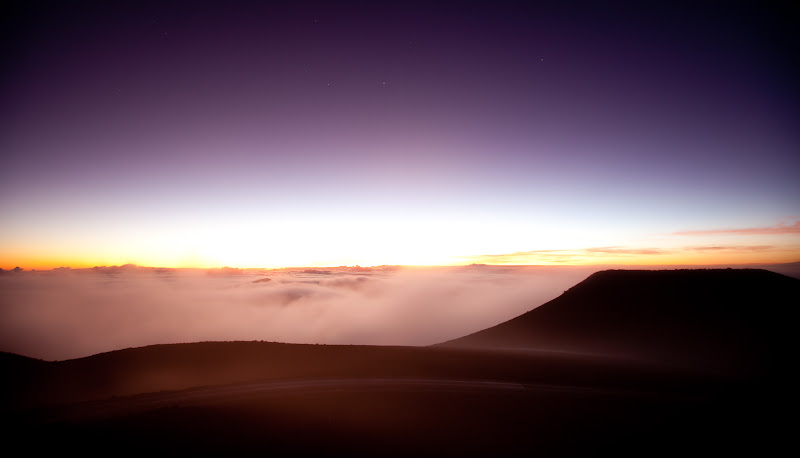 Photo: Sunrise over Haleakala  Since I posted a sunset picture in the morning, I figured I should post a sunrise picture at night. :)  This was taken from the peak of Haleakala, which you can see at the left side of this photo: https://plus.google.com/116594199576805510790/posts/5xjsSeZneJp  I learned a few things on the morning of this sunrise: 1.) Canon really means it when they say the 16-35mm is only weatherproof if you put a filter on it. 2.) You really want your lens to be weatherproof if you find yourself in the middle of a cloud. 3.) Moisture inside the lens can really ruin your morning. :)