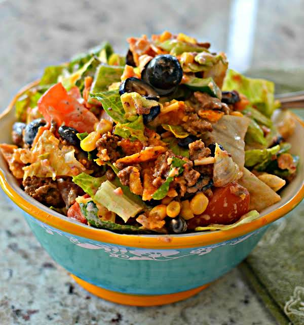 A Fun And Easy Taco Salad With Seasoned Ground Beef, Black Olives, Tomatoes, Corn, Black Beans, A Healthy Helping Of Cheese And Doritos Tortilla Chips.