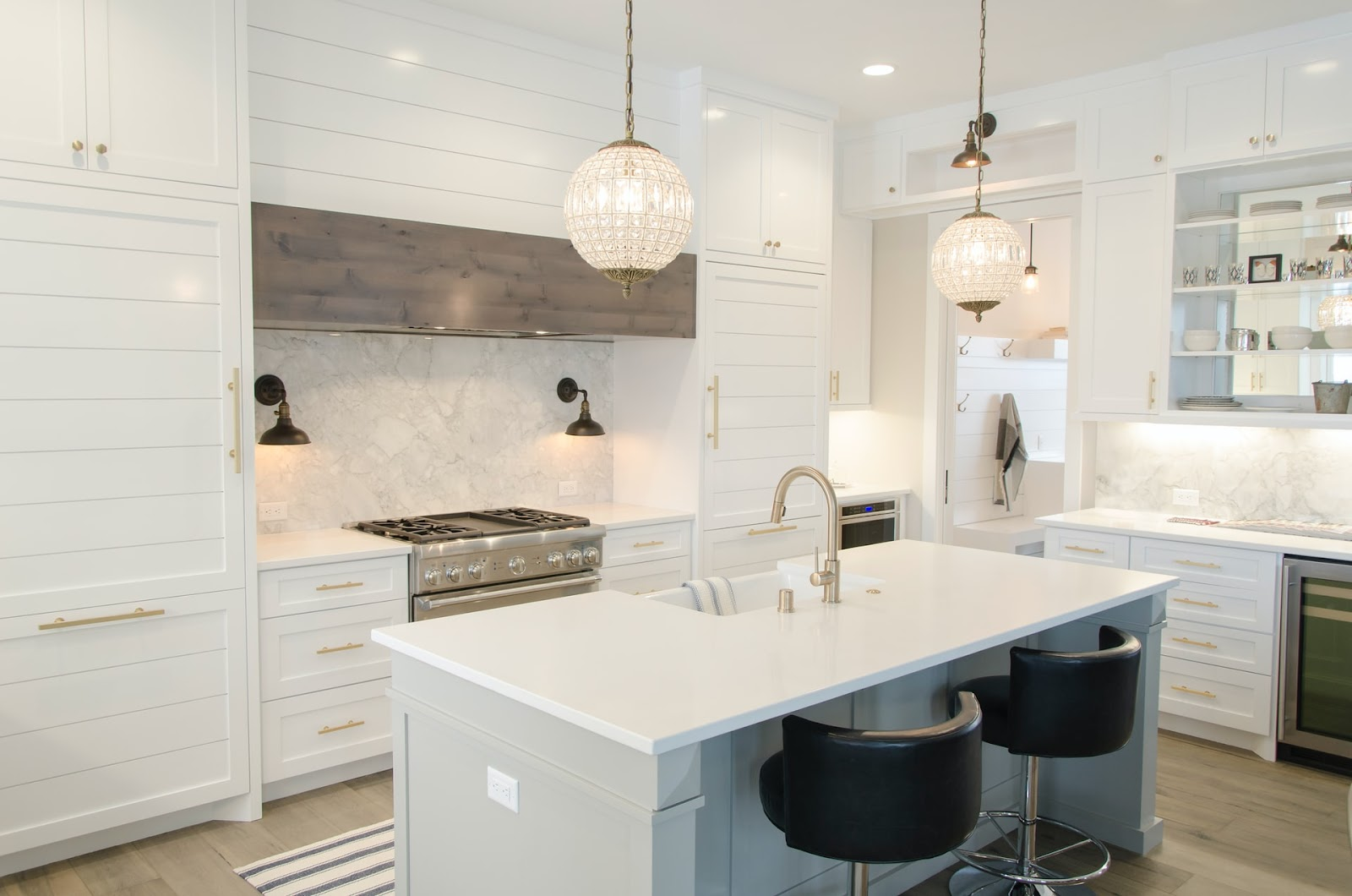 An all-white kitchen design with round-shaped pendant lights representing the importance of choosing the perfect kitchen cabinets