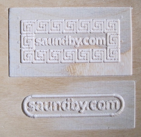 CNC router cut of saundby.com surrounded by a key pattern.