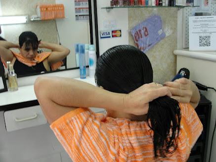 imagem da cabeleireira cortando o próprio cabelo